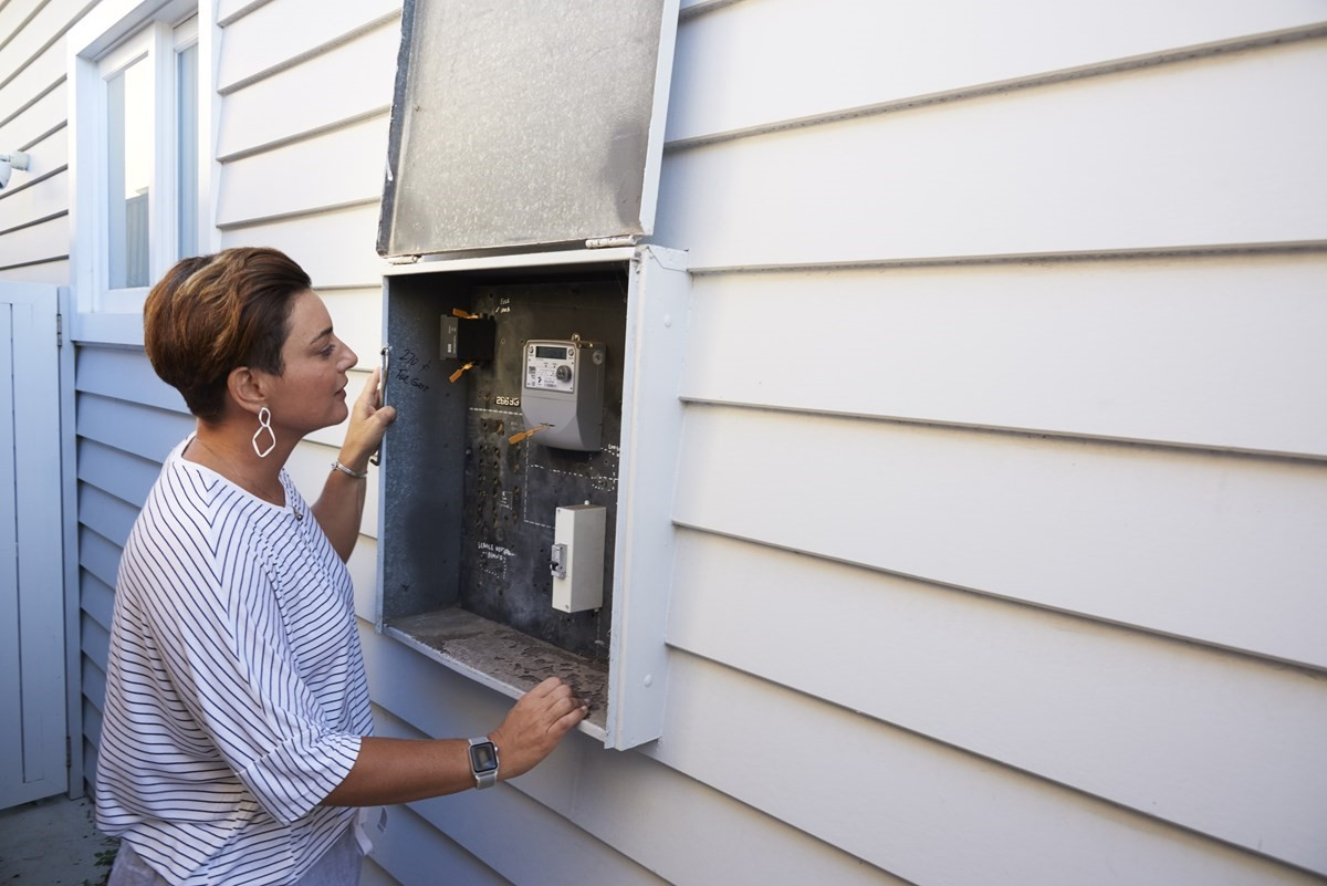 Person inspecting meter box.