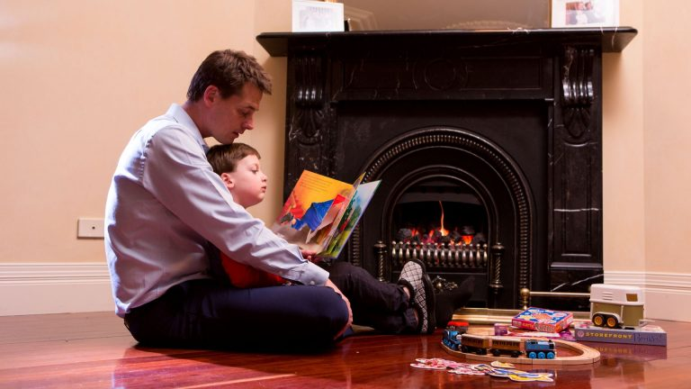 man-reading-to-child-in-front-of-gas-fireplace